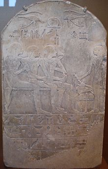 A stone stela with raised-relief images of a man seated with his son and wife, while a man stands to the right giving libations; Egyptian hieroglyphs are written in distinctly-marked horizontal columns at the bottom portion of the stela.