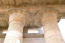 Two stone columns supporting a roof, painted with faded colors and incised with writing of Egyptian hieroglyphs