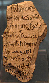 A light-colored stone fragment with hieratic handwriting in black ink scrawled on its surface