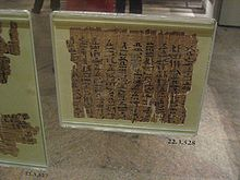 A museum display of an ancient fragment of a papyrus document safeguarded by sealed thick glass, with cursive hieratic handwriting in black ink on its surface