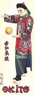 Tall, thin poster of a man in Chinese robes, posing with a golden ball floating between his hands.