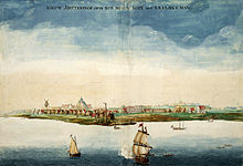 A painting of a coastline dotted with red roof houses and a windmill, with several masted ships sailing close to shore under blue sky.