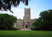 A Gothic style stone building with a central tower in front of a green field with trees on each side.