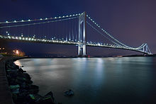 A tall suspension bridge connects a distant piece of land at night.