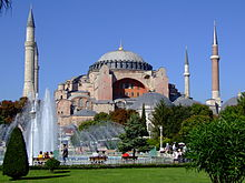 A reddish building topped by a large dome and surrounded by smaller domes and four towers