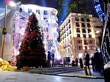 A large tree decorated under the night sky in red and green and surrounded by spotlights, city lights, and mid-rise buildings