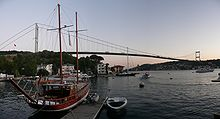 A docked sailboat floats in front of a suspension bridge, under twilight.