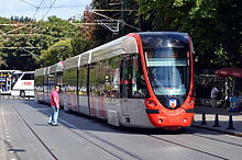 A red and silver electrified tram running through a street as a crossing pedestrian waits for it to pass