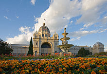 Ornate white building with an elevated dome in the middle, fronted by a golden fountain and orange flowers