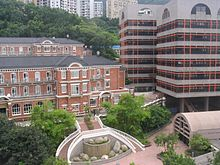 3-storey red brick building with gabled roof adjacent to 7-storey modern building with flat roof.