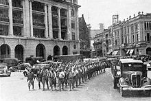 A parade of Japanese soldiers in a street of Singapore