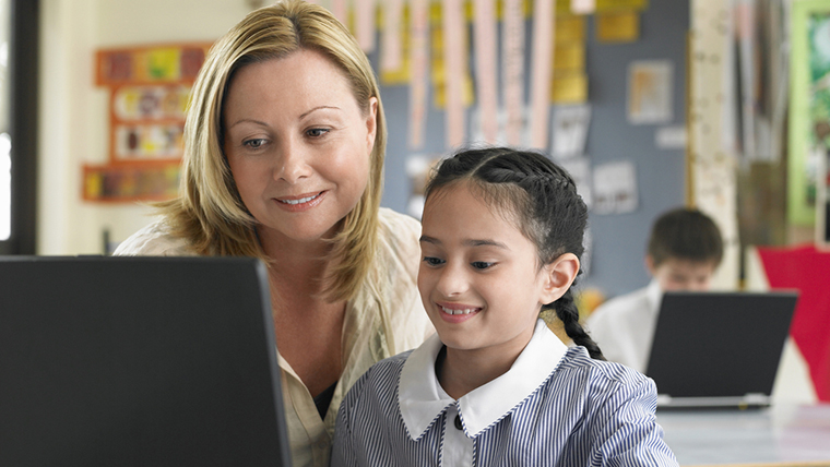 Student and teacher using computer
