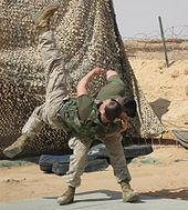 color photo of a Marine tossing another Marine over his shoulder onto a mat