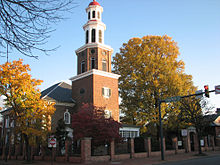 An 18th century red brick church with white steeple behind a modern road in autumn.