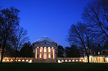 A red brick, Neoclassical dome with a large portico on the front and covered walkway on the sides lit up at dusk. Dark trees border the building on both sides.