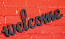 Welcome sign on red wall